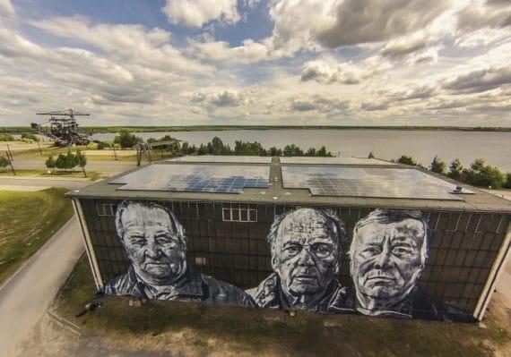 """Der Graffiti-Künstler Hendrik Beikirch bringt die Bergleute zurück nach Ferropolis - und überdimensionalen Portraits auf Hallenwänden sollen sie den Bezug zur Vergangenheit wieder herstellen. Die letzten Gesichter plant der Grafiker beim """"Splash""""-Festival fertig zu stellen."""
